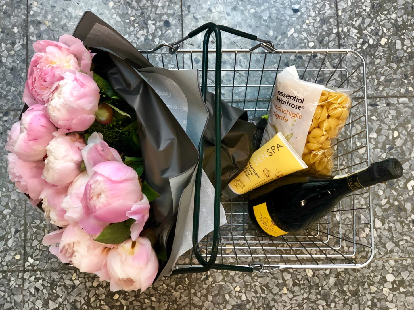 A shopping basket with flowers, body cream, pasta and prosecco